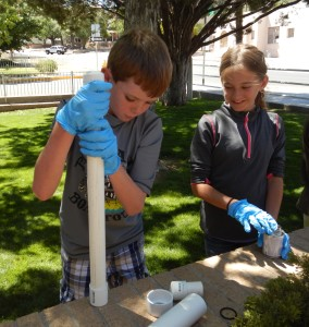 Young people glue together a water blaster during Youth DIY, summer 2014.