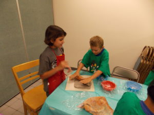 two children work on making an olla from clay in 2015