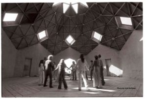 Courtesy photo of people holding hands in a circle in an octagonal building by Seth Roffman