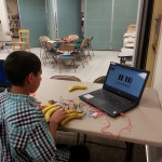 WildWorks participant uses the MakeyMakey to play piano with bananas