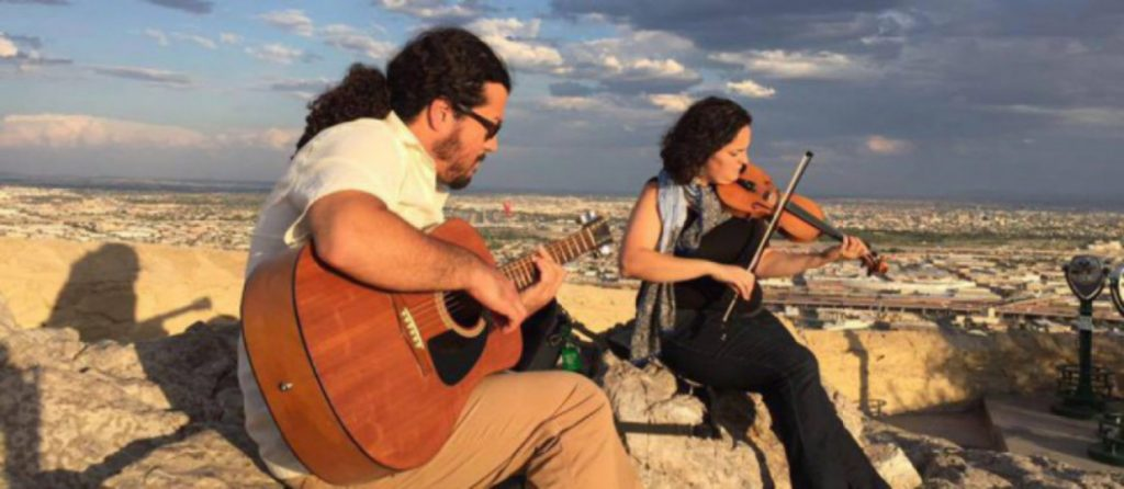 Maria and Yahví playing instruments on a mountain in the desert southwest