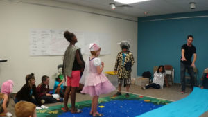 Children in costume perform a story they created with Santa Fe Opera educator Charles Gamble.