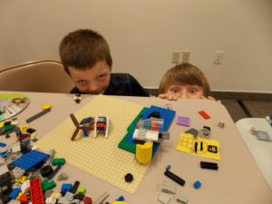 Two children peek from behind a table at Lego Club, summer 2016