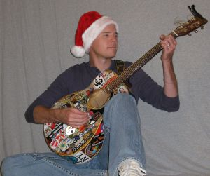Andy Mason wears and Santa hat and plays his guitar