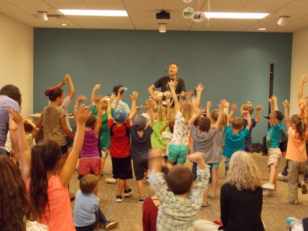 Children and family members raise their hands in the air during a concert with Andy Mason.