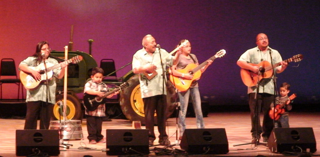 Cipriano Vigil and his family perform on stage.