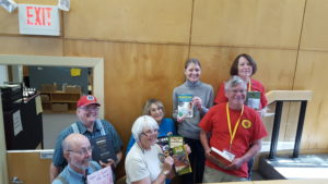 Rolling Stones Gem and Mineral Society members with library director Eileen Sullivan, holding geology books donated to the library