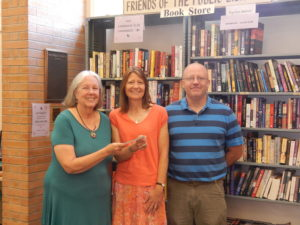 Friends of the Library representative Patricia Dunn presents a check to library director Eileen Sullivan and assistant director Ken Dayer.