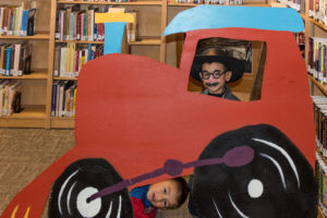 two children pose by a cardboard cutout train at the Love Your Library Day photo booth
