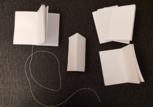 sections of folded paper laid out on a table and partially stitched together to make a book