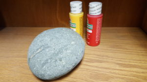 smooth rock next to two small bottles of paint
