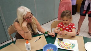Little Artist Club leader Donna helps a child glue fruity-flavored cereal to make a rainbow on paper.