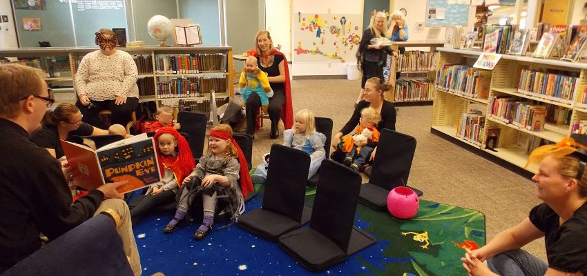 Children and caregivers listen to stories about Halloween.