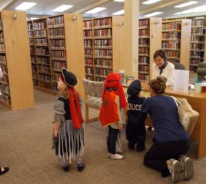children line up to trick-or-treat at the information desk