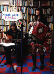 Members of the music group Auld Lang Syne play the guitar and accordian in a bookstore.