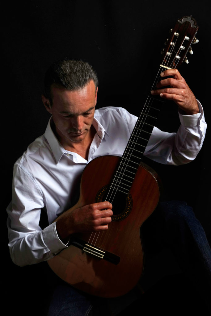 Portrait of Philippe Holmes facing forward playing guitar