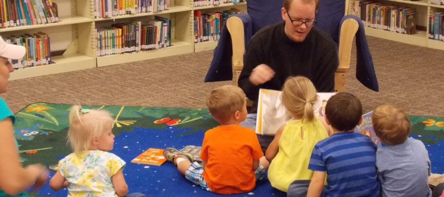 Chris reads a story to five small children